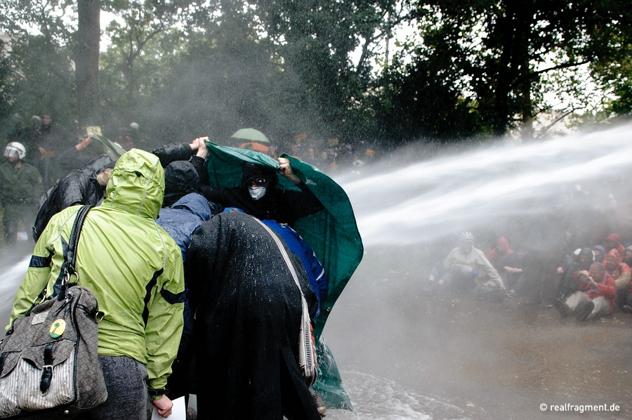 Demonstrators are trying to protect themselves against a water-cannon