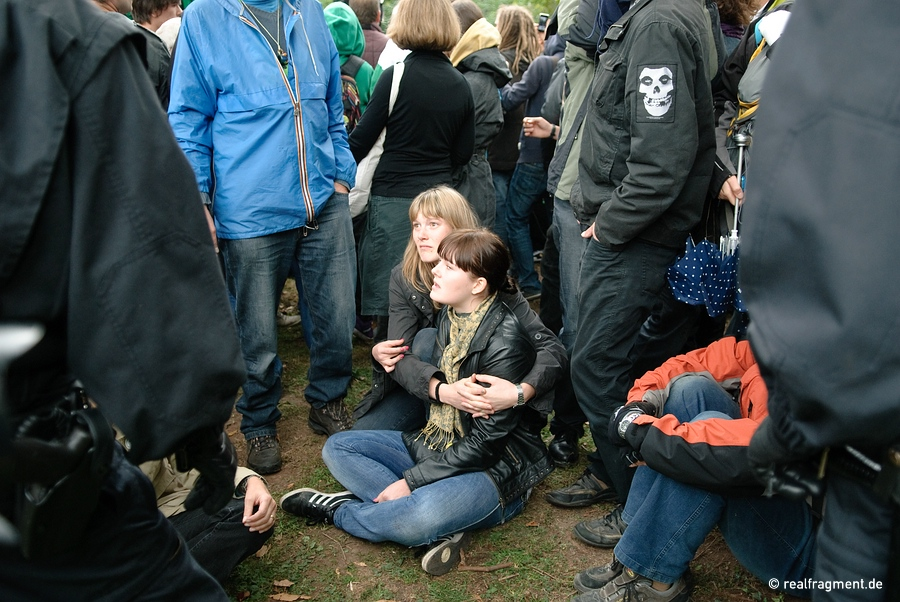 Two women are sitting down in front of a police line