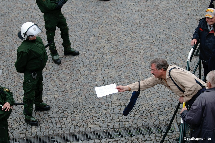 A demonstrator tries to hand over a flyer to a police man